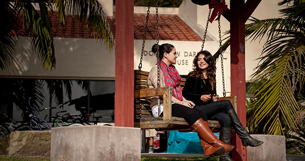 Two women conversing on a swing bench