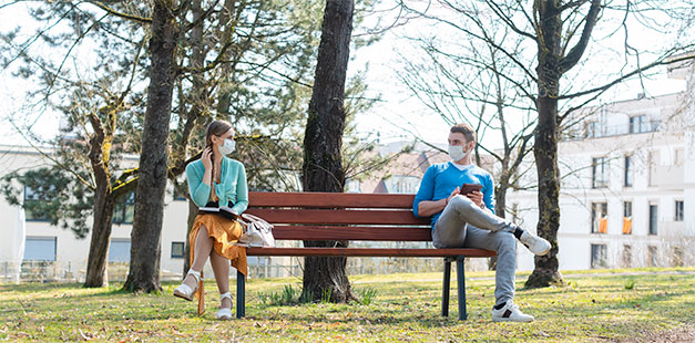 Park bench with two people practicing social distancing with face masks on
